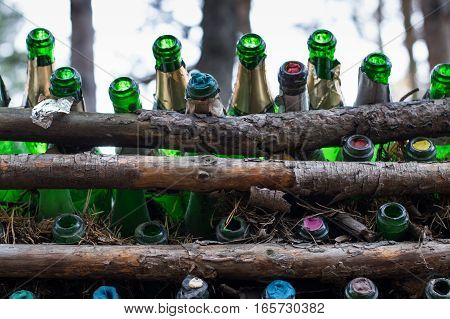Close up of empty green champagne bottles with foil and different colored stoppers placed between pine logs to make a fence. Located at the Eurasian line near Yekaterinburg Russia,  it is a popular wedding venue. Shallow depth of field.