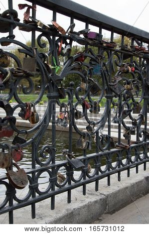 A length of black metal fence with multiple inscribed padlocks of different sizes, shapes and colors locked on it by couples to signify their love and commitment to marriage. The gray Iset River and riverbank located in Yekaterinburg Russia are seen throu