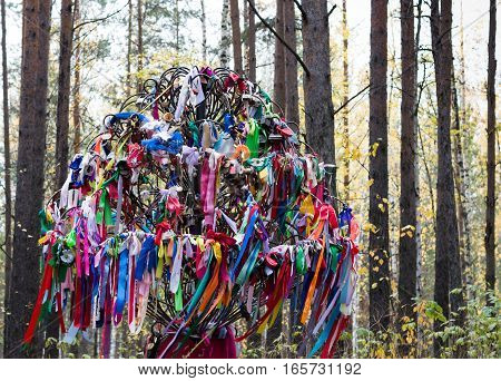 A large metal tree with multiple satin ribbons, locks and ties placed while making a wish, celebrating love and marriage or remembering the departed. Located in the forest at the Eurasian line, a popular wedding venue, near Yekaterinburg Russia.