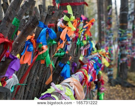 Close up of multiple satin ribbons tied on a log for luck, love, while making a wish or remembering the dead. Located at the Eurasian line at a popular wedding venue near Yekaterinburg Russia. Shallow depth of field.