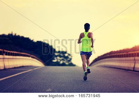 young fitness asian woman runner running on city road