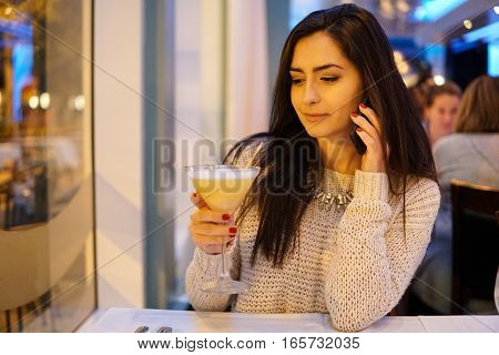 beautiful girl use  phone  in restaurant in the evening