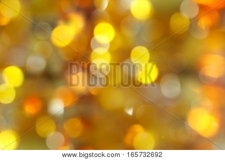 abstract blurred background - yellow, green and orange shimmering lights bokeh of amber