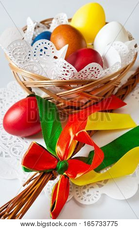 Traditional Czech easter decoration - regional whip with ribbons and decorated colorful eggs in the wicker scuttel on white background. Spring easter holiday arrangement.