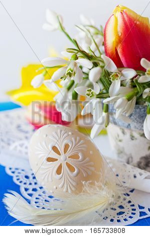 Traditional Czech easter decoration - flowerpot with snowdrops flowers and decorated perforated lacy eggs. Spring easter holiday arrangement.