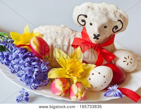 Traditional Czech easter decoration - white lamb cake with tulips hyacinth and daffodil lacy white eggs on white background. Spring easter holiday arrangement.