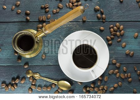 An overhead photo of a cup of black coffee on a wooden boards texture, with a vintage coffee pot, beans scattered around