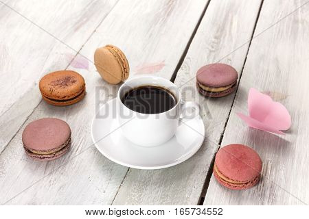 A photo of a cup of coffee with various pastel coloured macarons and paper butterflies, with a place for text