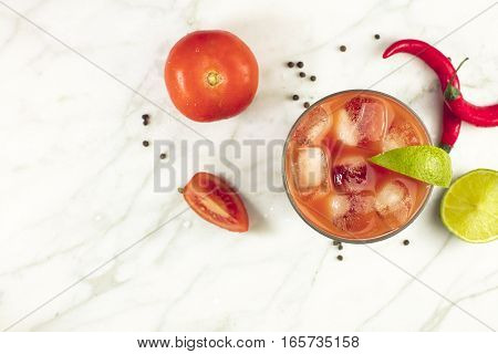 Bloody Mary cocktail, shot from above on a white marble texture, with red hot chili peppers, slices of lime, tomatoes, and copyspace