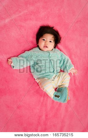 baby girl with cute teal sweater and hot pink background
