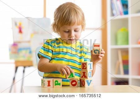 kid playing with block toys and learning letters