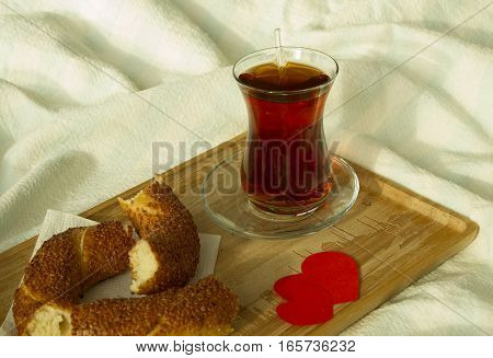 Morning turkish tea in traditional glass with bagel on the tray breakfast in bed