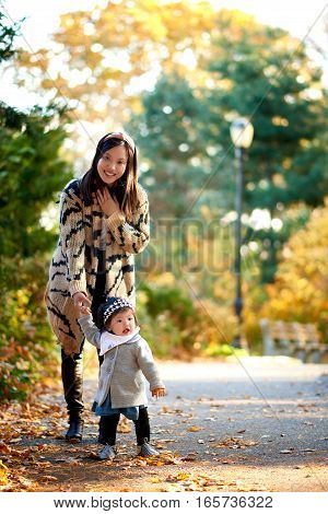 Mother holding daughter in stunning fall scene