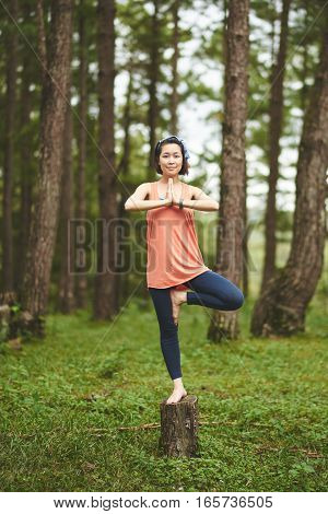 Vietnamese young woman standing on stump in tree pose