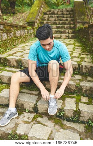 Sporty young Asian man tying shoes before jogging