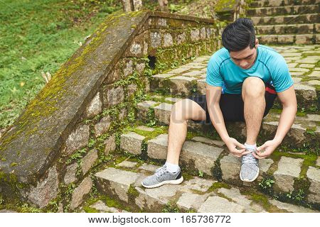 Young man sitting on steps and tying sportshoes before running