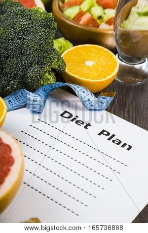Food And Sheet Of Paper With A Diet Plan On A Dark Wooden Table. Concept Of Diet And Healthy Lifesty
