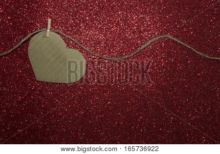 One carton heart attached to the rope on red shining background