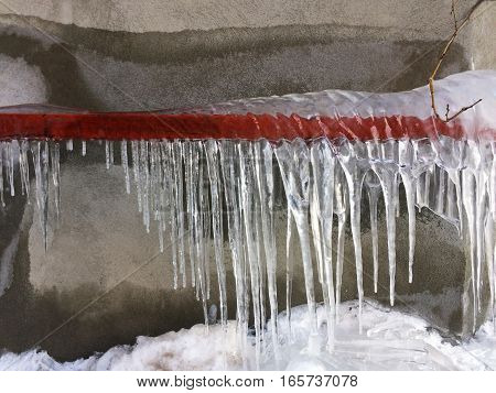 Icicles hanging on red frozen metal pipe
