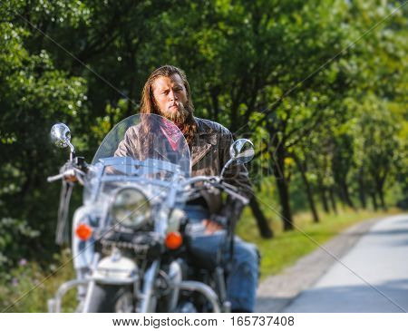 Portrait Of Biker Man With Beard Sitting On His Motorcycle
