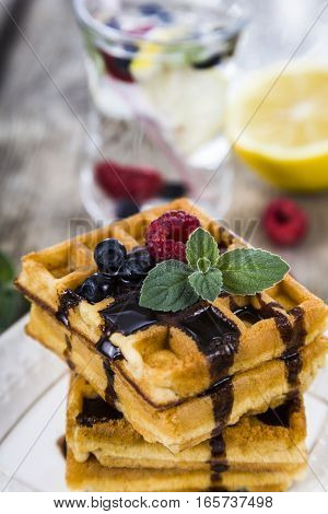 Delicious waffle with berries and chocolate on wooden table. Belgian waffles with raspberries blueberries and mint covered with liquid chocolate.
