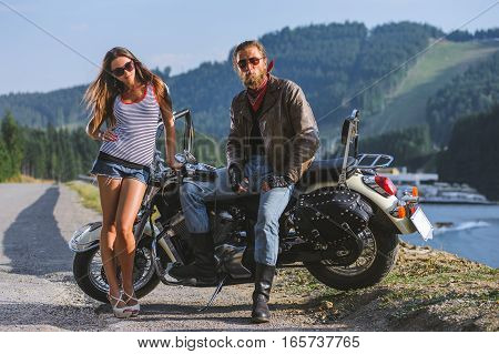 Couple Standing By A Motorbike