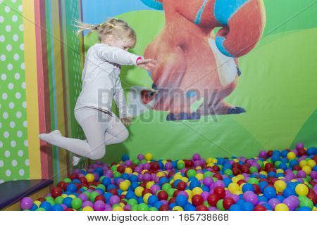 4 years old girl jumping into the colorful balls. playing in the park playground.