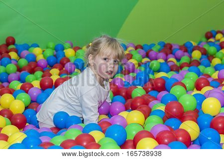 little smiling girl 3-4 years playing in colorful balls park playground