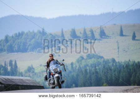 Biker Driving His Cruiser Motorcycle On Road