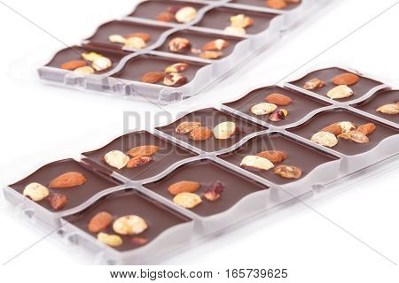 Chocolate with assortment nuts in plastic boxes on white background.