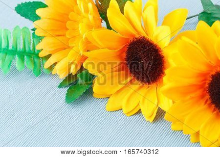 Yellow fabric daisies on blue cloth background.