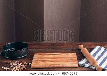 Clean workplace of baker with tools free space. Kitchen table with wooden board, pin, pie form and dry fruits waiting for confectioner, copy space for text