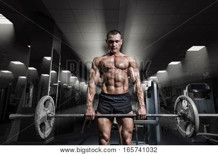 Muscular man workout with barbell at gym. Deadlift barbells workout. Brutal bodybuilder athletic man perfect abs shoulders biceps triceps and chest.
