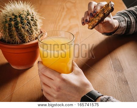 Girl Holding A Glass Of Juice And Eating Cookies.