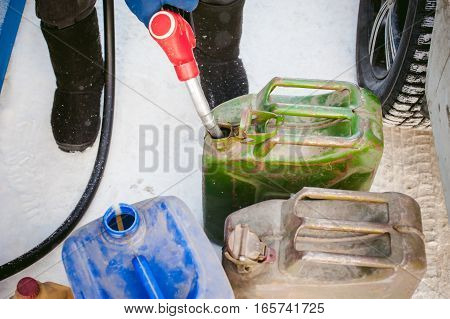 Adult Man Fills A Car With Petrol At A Fuel Station In The Winter. Refueling Nozzle Man Holding In H