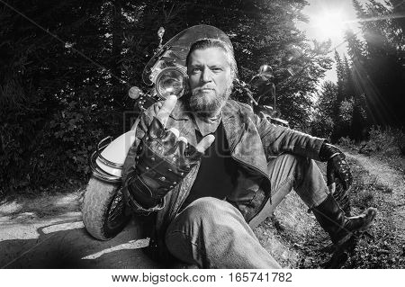 Unshaven Male Biker Sitting On Dirt Road Near Motorcycle