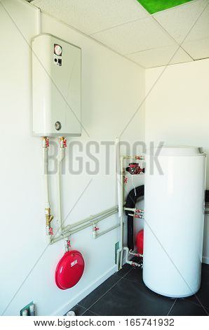 A domestic household boiler room with a new modern gas boiler heating electric warm water system and pipes