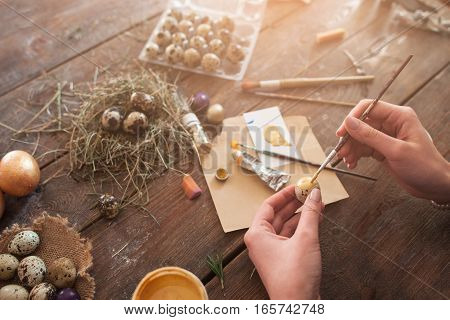 Woman coloring Easter eggs at home. Top view on female hands with egg and paintbrush, decorating eggs for holiday, artisan pov. Tradition, handmade, art concept