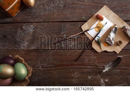 Art tools and colorful Easter eggs flat lay. Top view on rustic dark wooden background with dye and paintbrushes, after decorating eggs for holiday. Creative, handmade decoration, tradition concept
