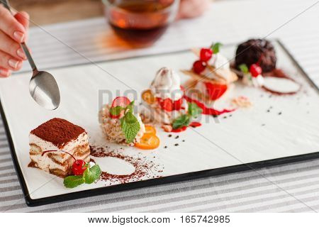 Tasting one cake from lots, close-up. Plate with five different sweet desserts, hand taking one. Degustation, choosing dessert for party or wedding, gastronomy, event organization concept