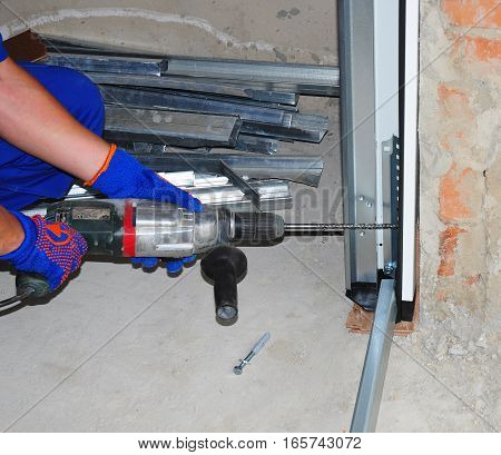 Repairman Installing Garage Door. Contractor Using Drill and Metal Anchor Bolt to Attach Plastic and Metal Profil Section Garage Door Panel to Wall.