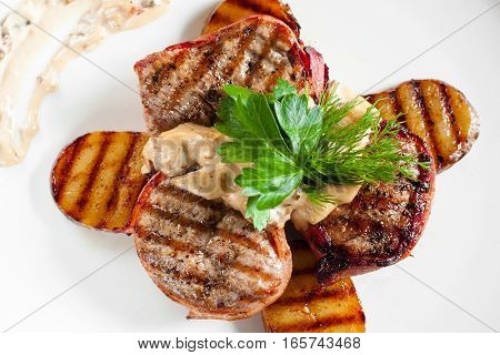 Grilled steaks and potatoes on white flat lay. Top view on plate with barbecue pork chops and vegetables with mushroom sauce. Dining, junk food, restaurant menu concept