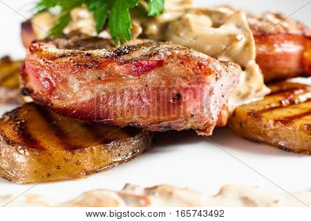 Juicy grilled steak on plate side view.. Close-up of barbecue pork chop served with potato and creamy sauce. Meat meal background. Dining, junk food, restaurant menu concept
