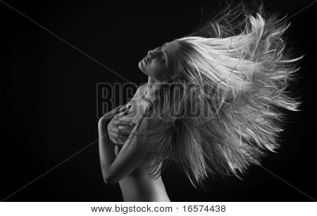 Portrait of a beautiful young woman with flying blond hair