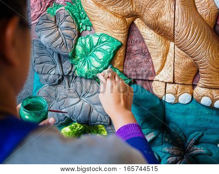 Hand of artist painting asia elephant and tree