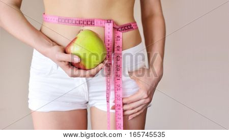 Young Woman Is Measuring Body And Hold Apple