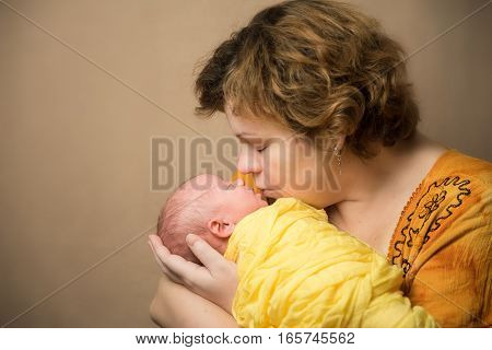 Mother kissing newborn baby. Yellow colored clothes