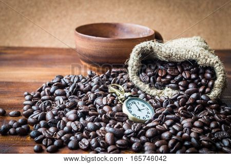 It's time to coffee Coffee bean heap on wood floor with hemp bags and coffee cup