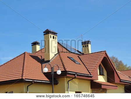 Closeup of solar panel on red tiled house roof with skylights chimney and roof window. Roofing Construction.