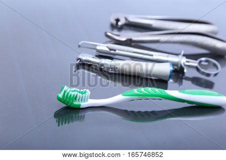 dental care toothbrush with dentist tools on mirror background